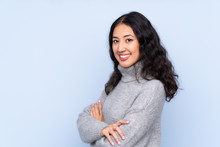 Spanish Chinese Woman Over Isolated Blue Background With Arms Crossed And Looking Forward