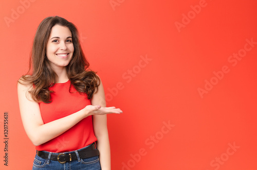 Obraz young pretty woman smiling cheerfully, feeling happy and showing a concept in copy space with palm of hand against red wall - fototapety do salonu