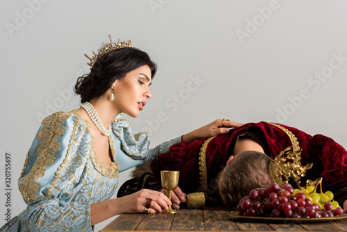 sad queen with crown looking at killed king isolated on grey