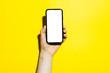 Leinwanddruck Bild - Close-up of male hand holding smartphone with  mockup, isolated on yellow background.