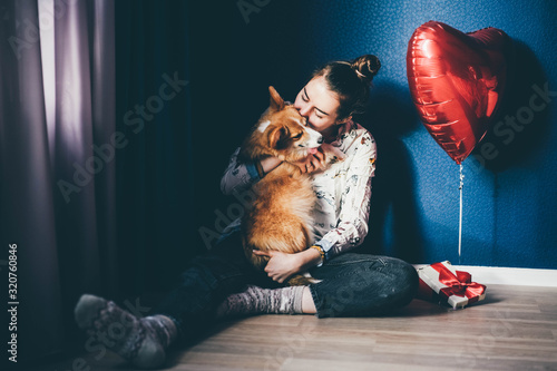 A happy girl holding a small light puppy with a red ribbon Canvas Print