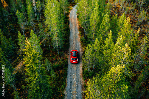 Fototapeta Aerial view of red car with a roof rack on a country road in Finland