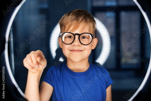 Fototapeta future technology, virtual reality and vision concept - happy smiling boy in glasses touching something invisible over white illumination in dark room obraz