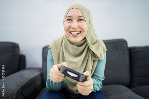 Fotografía Beautiful muslim woman playing console games at her couch.
