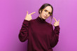 Leinwanddruck Bild - young pretty woman with a bad attitude looking proud and aggressive, pointing upwards or making fun sign with hands against purple wall