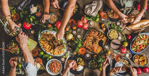 Fototapeta Turkish cuisine family feast. Flat-lay of peoples hands and lamb chops with quince, beans, salad, babaganush, rice pilav, pumpkin dessert, lemonade over rustic table, top view. Middle East cuisine obraz