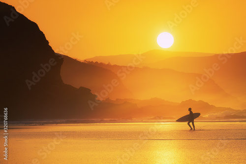 surfer exiting water at misty sunset