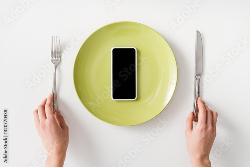 Top view of female hands with cutlery and smartphone on plate on white background