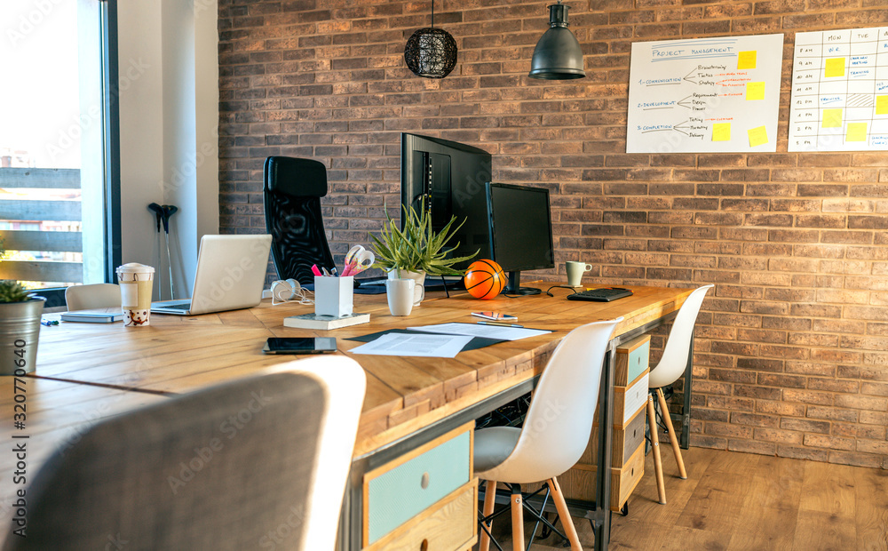 Fototapeta Interior of industrial style coworking office with various workplaces