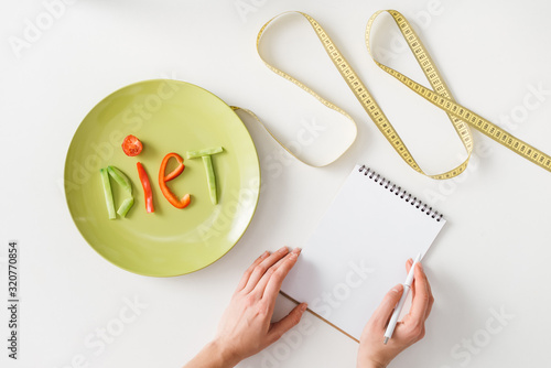 Top view of woman writing in notebook near measuring tape and plate with diet lettering from vegetable slices on white background