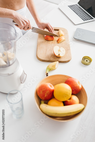 High angle view of woman cutting fruits for smoothie with measuring tape, scales and laptop on kitchen table, calorie counting diet