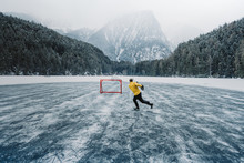 Ice Hockey Player Shoots And Scores. Player On A Frozen Pond. Skates On Player Feet During Ice Hockey. Hockey Player Practising On A Frozen Pond Outdoor.