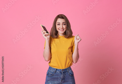 Fototapeta Portrait of happy young woman holding mobile phone isolated over pink background. obraz