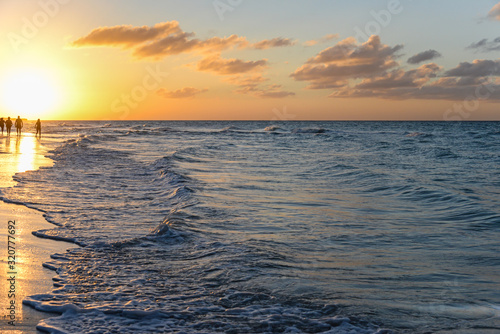 Silhouettes of people at sunset on the beach of Atlantic ocean, Cuba Fototapeta