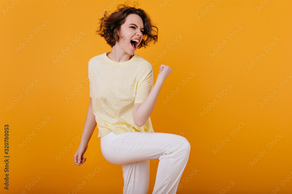 Fototapeta Pretty excited european woman funny dancing in studio with orange interior. Indoor photo of enthusiastic curly girl in white atiire spending time at home.