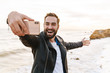 canvas print picture - Image of young man taking selfie on smartphone while walking by seaside