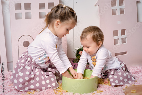 Fototapeta Two sisters 1 and 3 years old girls sits on the floor in the kitchen and plays with dry pasta. obraz