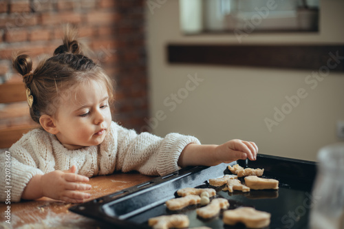 Fototapeta Mother and daughter baking cookies in their kitchen obraz