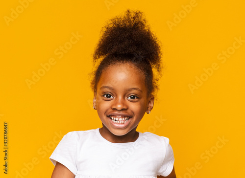 Obraz Portrait of african little girl smiling over yellow background - fototapety do salonu