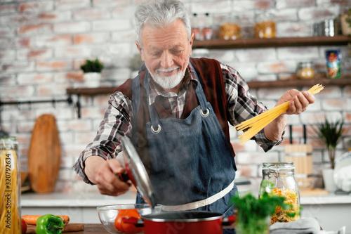 Man in kitchen. Old man cooking pasta. Canvas Print