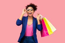 Excited Black Woman Holding Shopping Bags At Pink Studio