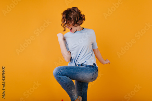 Refined short-haired lady wears dark-blue jeans jumping in studio. Attractive girl with wavy hairstyle dancing on yellow background.