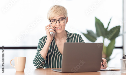 Woman Talking On Mobile Phone Using Laptop Working In Office