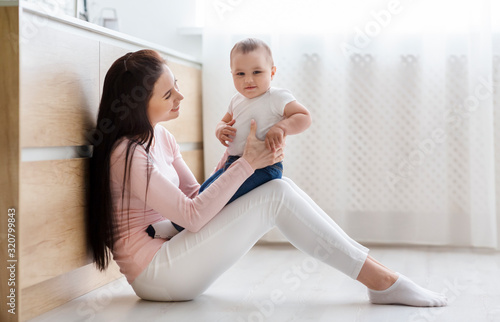 Happy mother playing with her cute baby son on kitchen floor