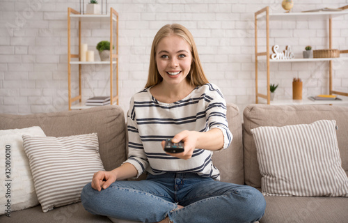 Young attractive woman watching TV at home