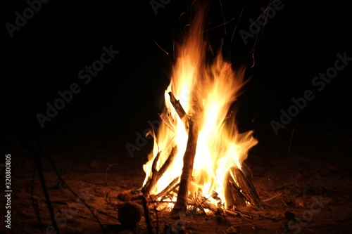 Wide shot of blazing flames from a bonfire, dark background