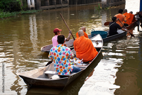 Thai people praying put food and thing offerings to monks procession on boat in Canvas Print