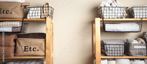 Fototapeta Bed sheets, duvet covers and towels are folded vertically. Metal and fabric black baskets. The concept of housework and storage. obraz