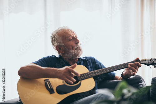 Fototapeta The old man and his guitar in the house