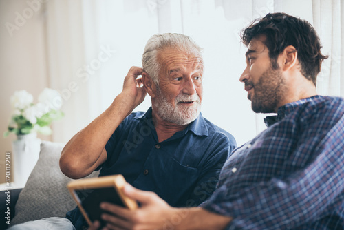 Obraz An adult hipster son and old senior father stay for work at home, two generations have a beard talking together and relaxing with smile, happy and enjoy living to isolation quarantine at home - fototapety do salonu
