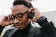 Close-up portrait of adorable black man with stylish haircut listening music with eyes closed. Photo of tired african guy in glasses enjoying song in headphones.