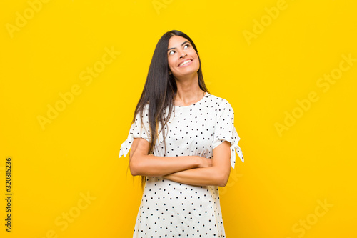 young pretty latin woman feeling happy, proud and hopeful, wondering or thinking Wallpaper Mural