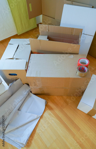 Fotografering vertical close up view of moving boxes and materials on a wooden parquet floor