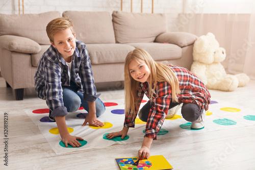 Fototapeta Cheerful siblings playing twister game on floor having fun indoor