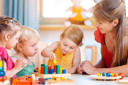 Obraz Group of children and teacher playing in kindergarten - fototapety do salonu