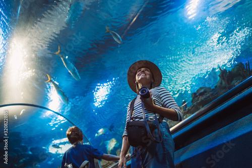 Photo Young female with modern photo camera walking in indoor huge aquarium tunnel, enjoying a underwater sea inhabitants