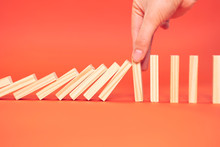 Hand Finger Stops Falling Wooden Dominoes, Red Background, Domino Principle, Business Concept