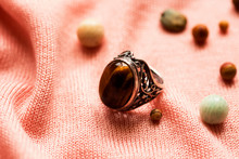 "Old Vintage Grandma's Ring With ""tiger-eye"" Gemstone On A Pink Fabric Background"