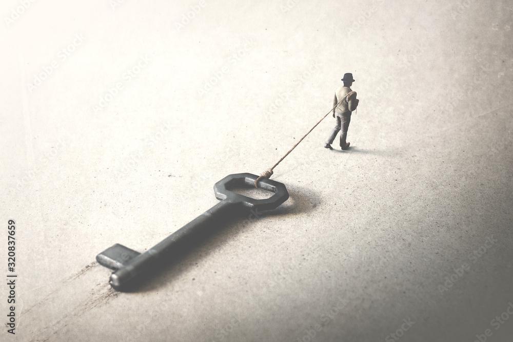 Fototapeta man dragging a big heavy key, surreal concept