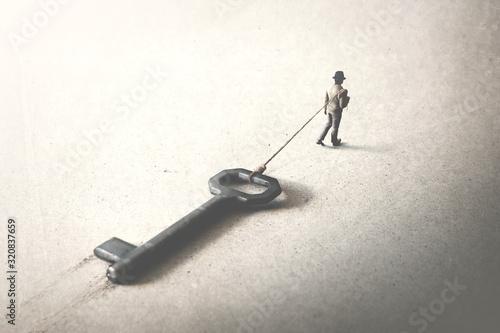 man dragging a big heavy key, surreal concept Canvas Print