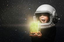 A Small Child Holds Plants In An Airplane Helmet. The Child Looks At The Grass Through The Glass.