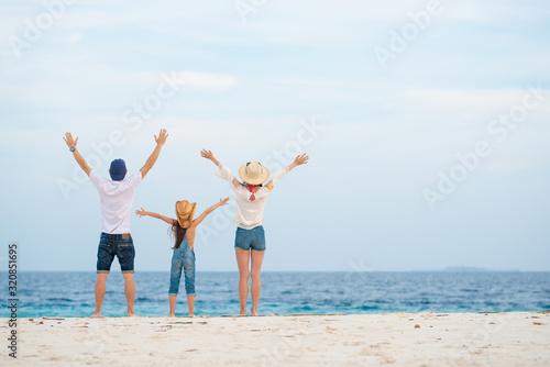 Fotografija ビーチで両手を広げる父と母と娘