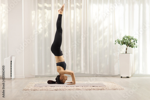 Young woman making a headstand on a mat Canvas-taulu