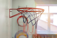 Basketball Hoop With Blue Net Hanging On Wall In Gym