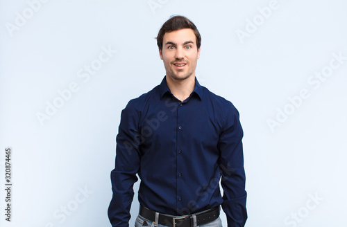young handsome man looking happy and goofy with a broad, fun, loony smile and ey Wallpaper Mural