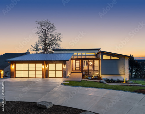 Foto Beautiful modern style luxury home exterior at sunset with glowing interior lights
